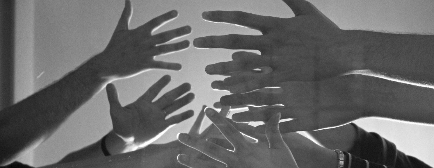 Kuvassa nuorten käsiä yhdessä ilmaan nostettuina.