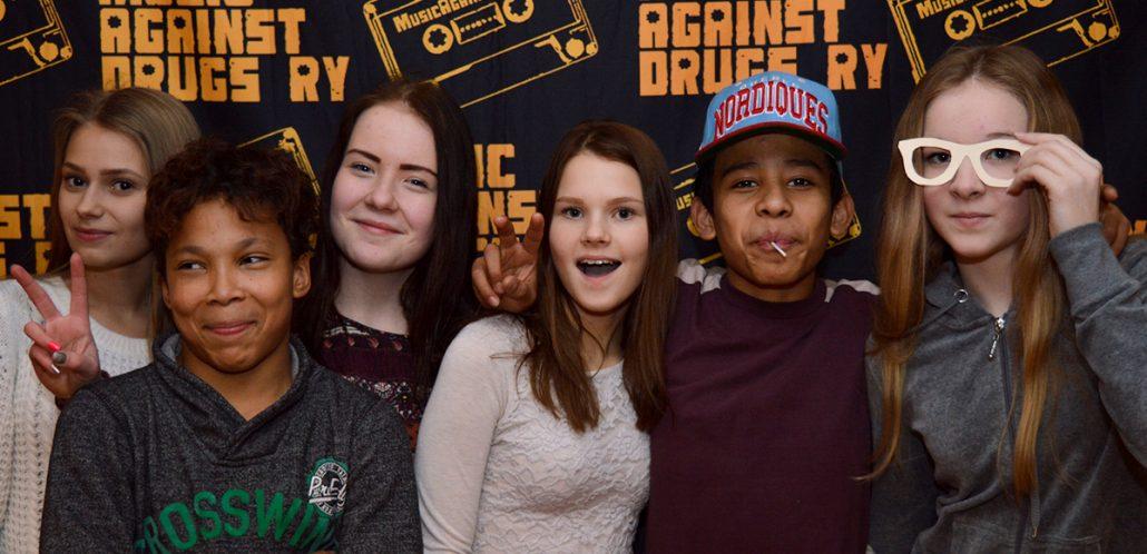 Kuusi yläkouluikäistä nuorta seisoo vierekkäin ja hymyilee Music Against Drugs -iltatapahtumassa.
