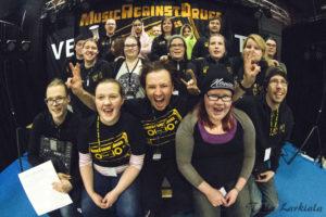 Yhteiskuvassa hymyileviä nuoria ja työntekijöitä Music Against Drugs -iltatapahtuman jälkeen.