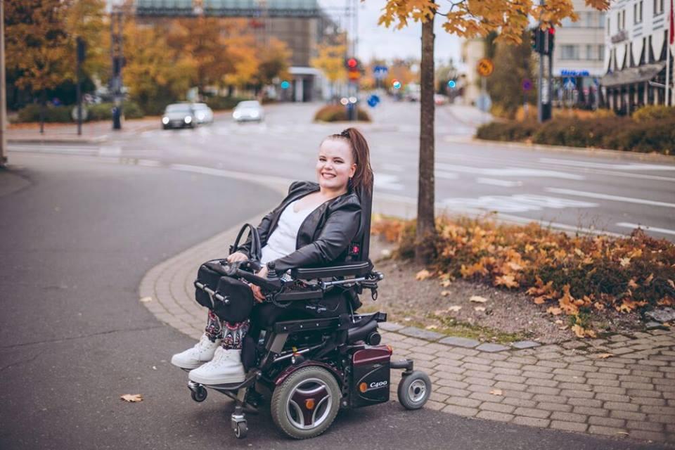 pyörätuolissa istuva nuori ulkona.