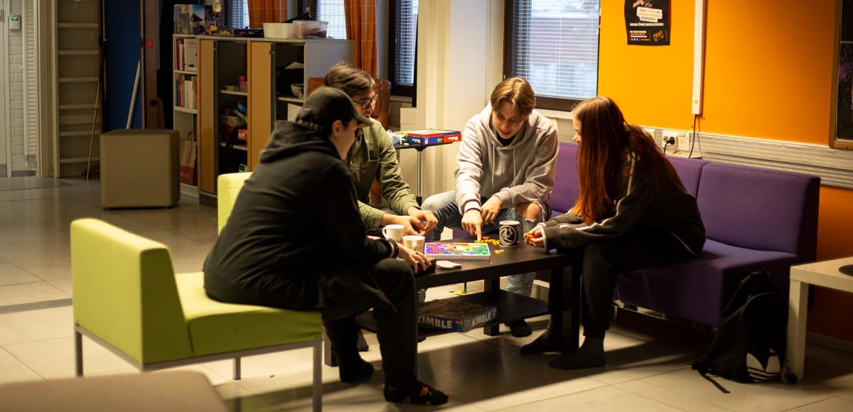 Nuoria olohuoneessa, pöydän äärellä pelaamassa. Kuvan on ottanut Ink-tiimiin osallistunut Jenna-Julia Mäenpää.