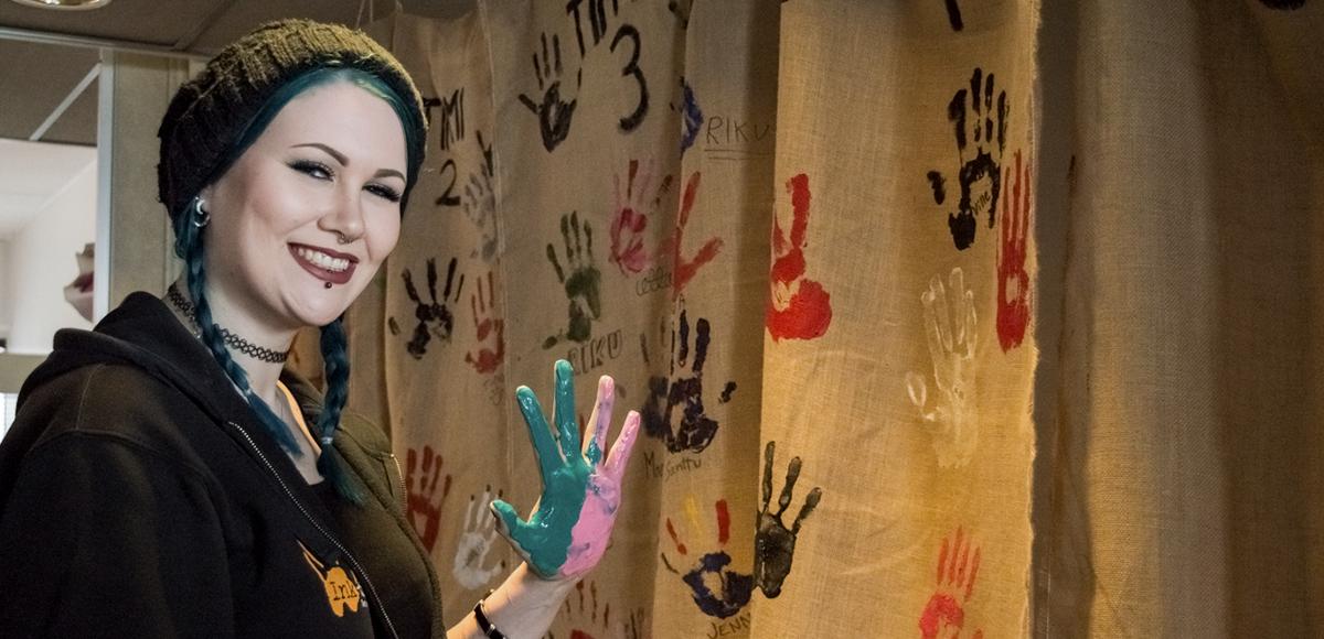 Hymyilevä nuori jättämässä kädenjälkensä maalilla toimiston seinäkankaalle.