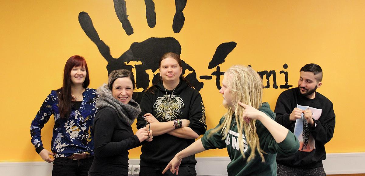 Tiimiläisiä poseeraamassa Ink-tiimin logolla koristellun seinän ääressä.