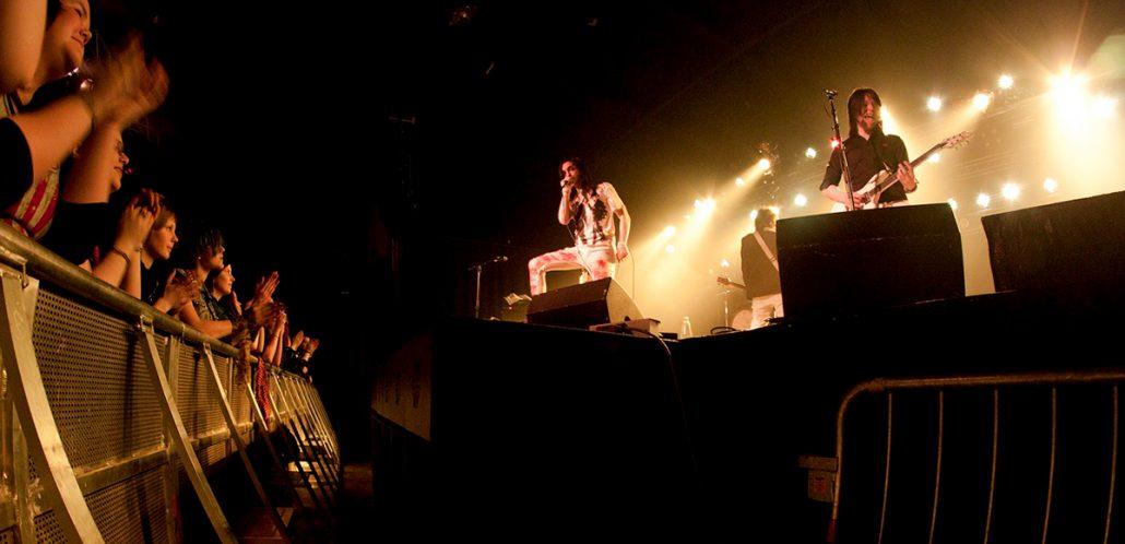 Kuvassa on iltatapahtumassa esiintyvä yhtye lavalla ja yleisö.