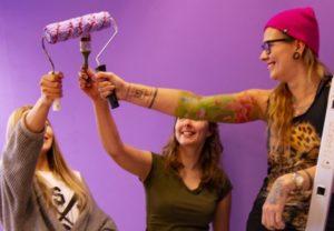 Kolme hymyilevää yhteiskunnallisen markkinoinnin tiimin nuorta tiimihuoneen seinän maalauspuuhissa.