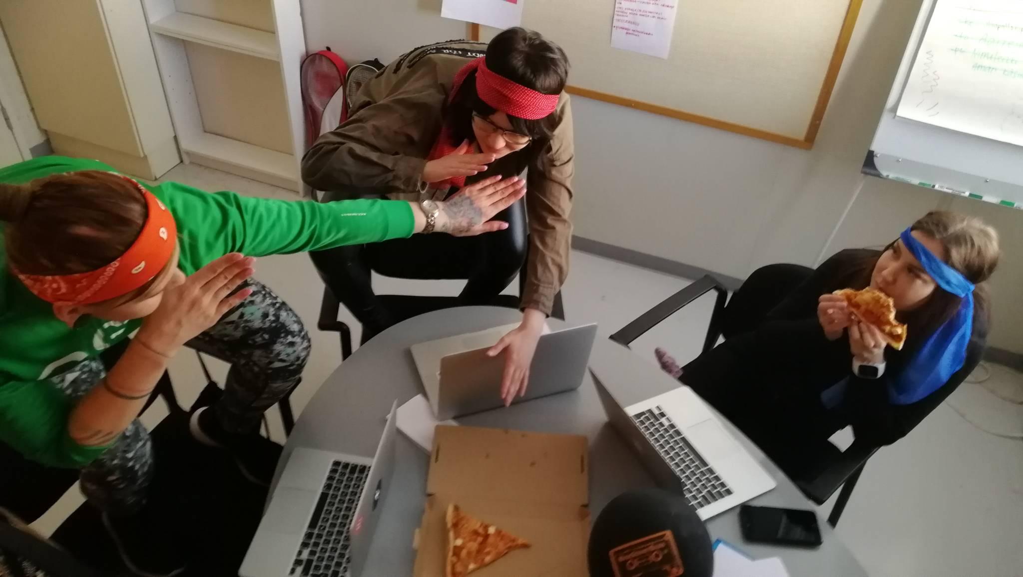 nuoria syömässä pitsaa. kaikilla värikäs otsanauha.
