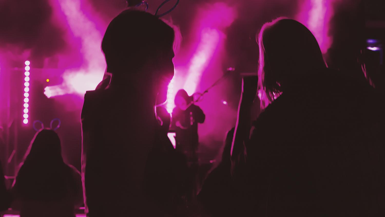yleisöä ja yhtye lavalla iltatapahtumassa. Vaaleanpunainen valo.