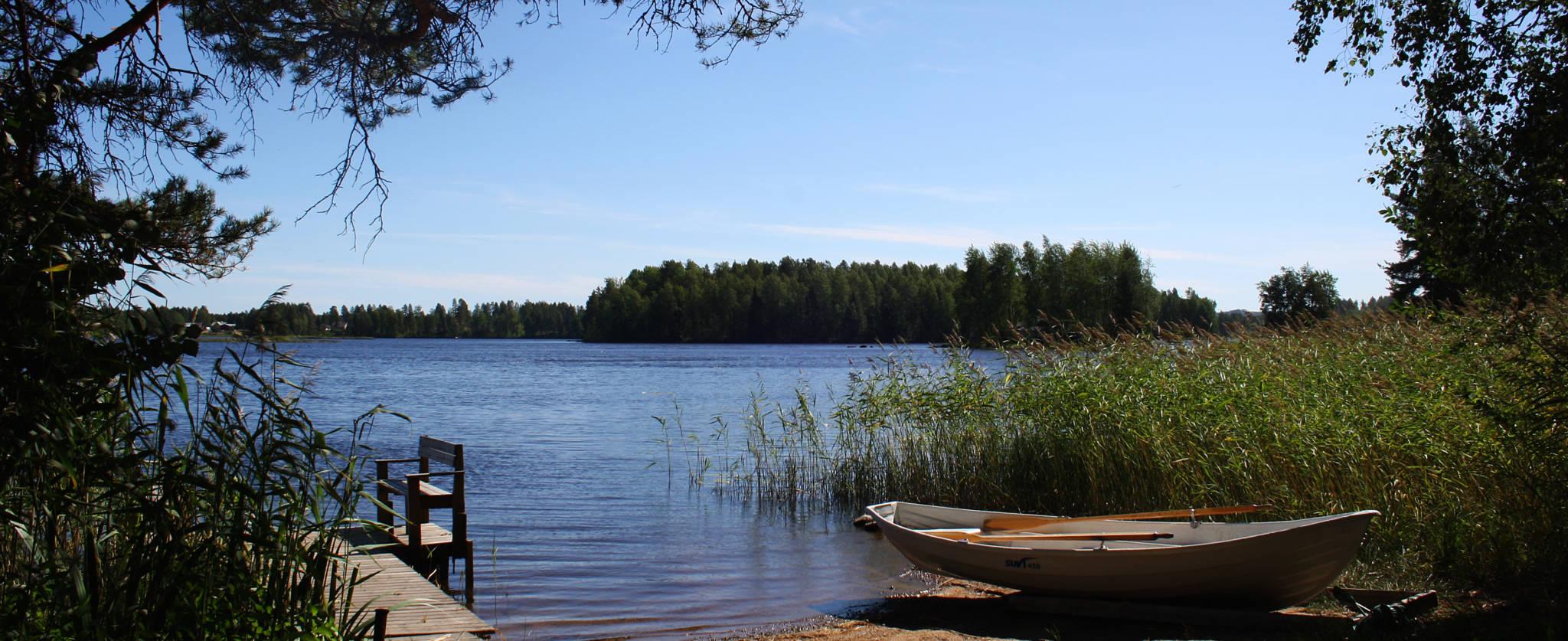 järvi, kaislikko, laituri ja vene kesäpäivänä