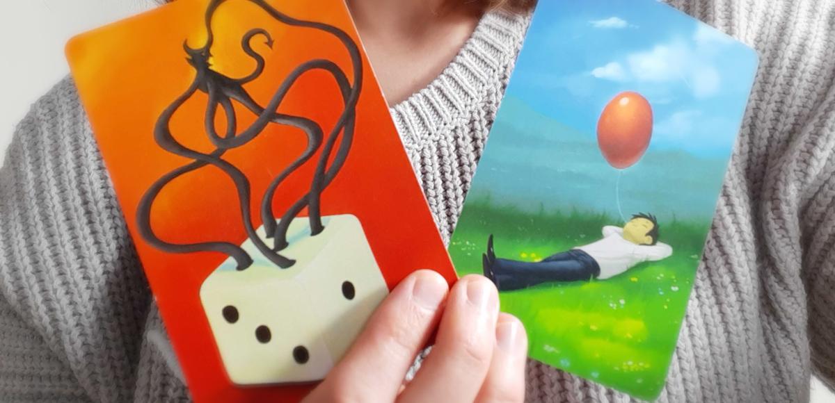 käsi pitelee kahta korttia. Toisessa nurmikolla makaileva ihminen, jolla suussa naru, jonka päässä ilmapallo. Toisessa kortissa arpakuutio, josta kasvaa lonkeromainen paholainen.