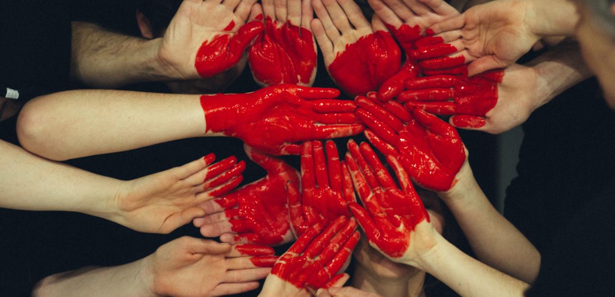 käsiä, joista osa maalattu punaiseksi siten, että syntyy sydämen-kuva