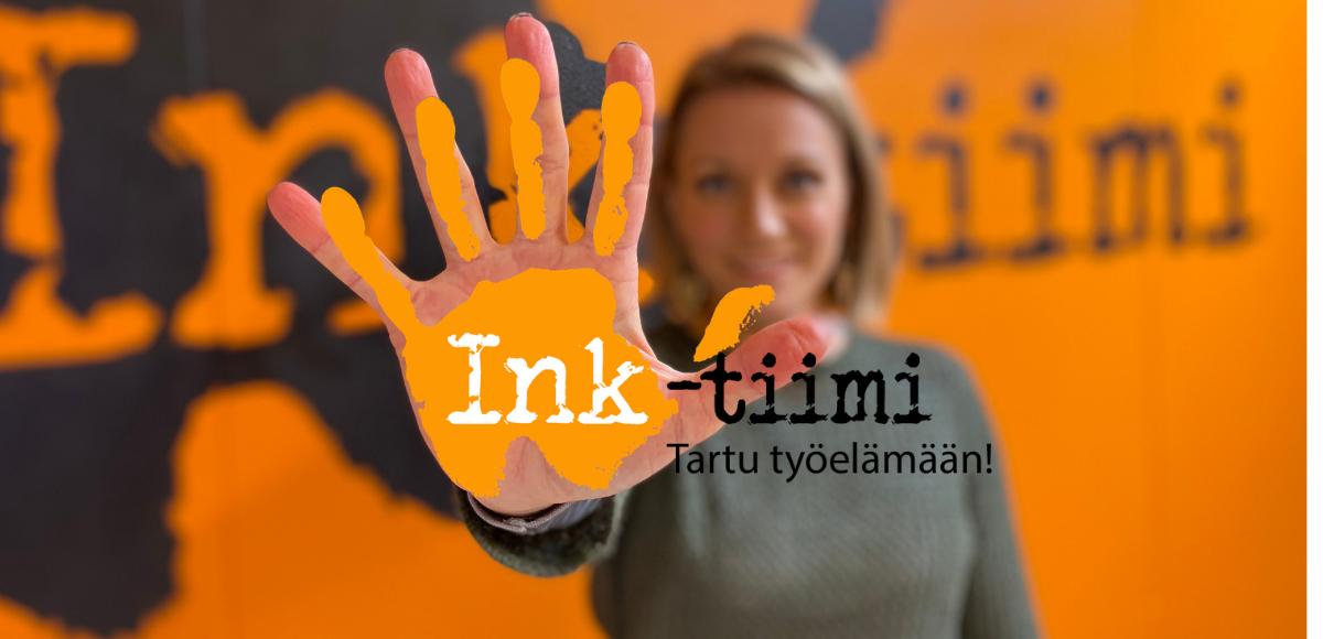 Tiimipäällikkö Sanna Huovila pitää kättä kuvan etualalla. Käden päälle kuvattu Ink-tiimin kämmenenmallinen logo.