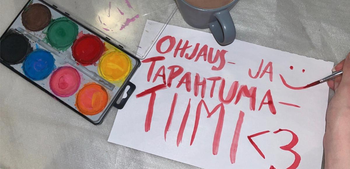 Valokuva vesiväripalerista, kahvikupista. Reunassa näkyy käsi, joka juuri maalannut punaisella vesivärillä paperille tekstin Ohjaus- ja tapahtumatiimi. Paperille piirretty myös hymynaama ja sydän.