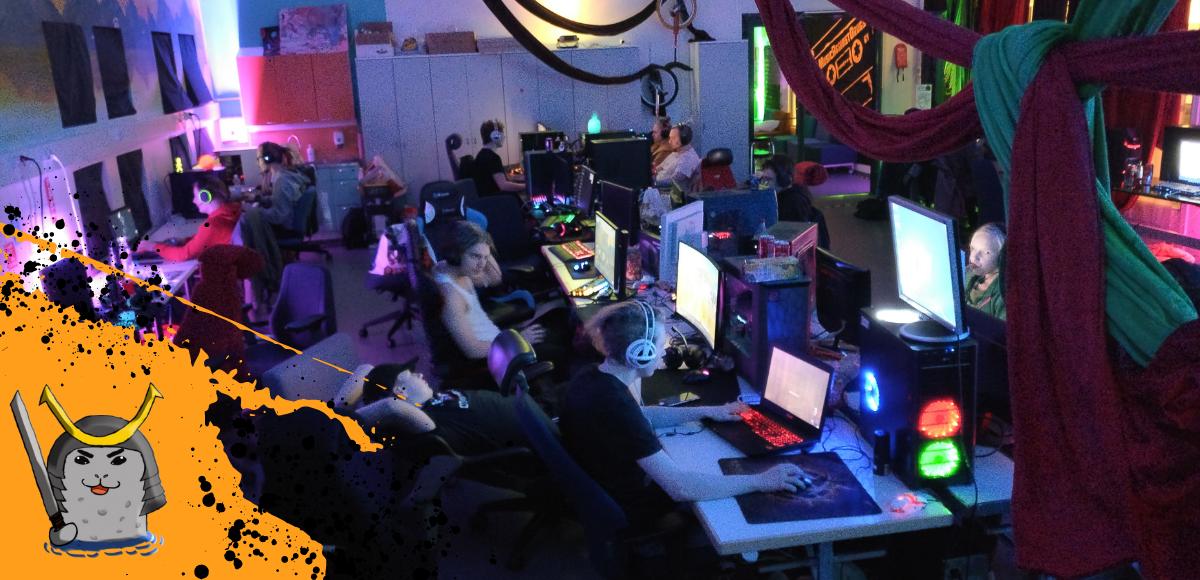 Ihmisiä pelaamassa neonvaloin valaistussa huoneessa. Isgee-toiminnan logo.