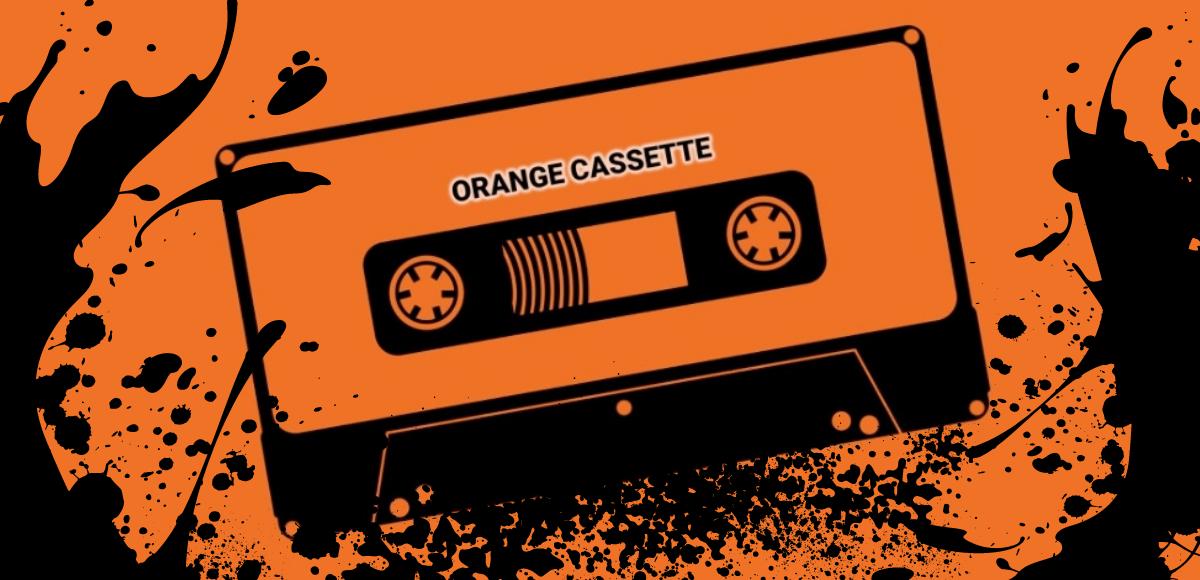 Piirretty kasetti oranssilla pohjalla. Kasetissa teksti Orange Cassette ja kasetista mustia roiskeita.